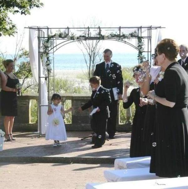 The flower girl and ring bearer walk up the aisle at the Harkness Amphitheater wedding.