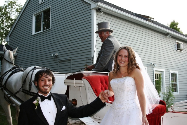 The groom helps the bride down from the horse-drawn carriage before their backyard wedding.