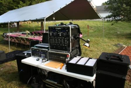 The DJ at the meadow wedding reception was between the wedding reception tent and the dance floor.