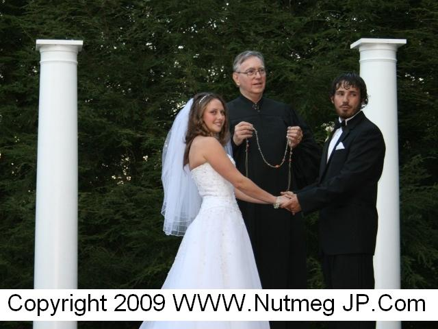 Handfasting as part of an outdoor wedding in New London County